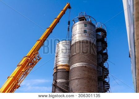 Crane is carry and keeps balance with heavy metal silo in industrial complex. poster