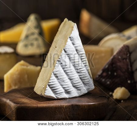 Segment of  Brie cheese or soft cow's - milk  French cheese on wooden board. Different cheeses at the background.