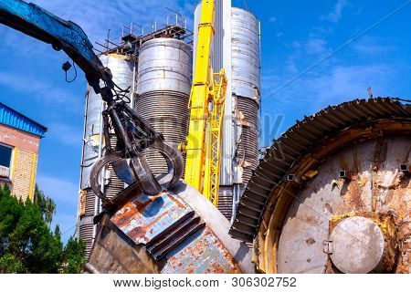 View on machine, loader manipulator with hydraulic grappling claw until is collecting, moving old steel, scrap metal. poster