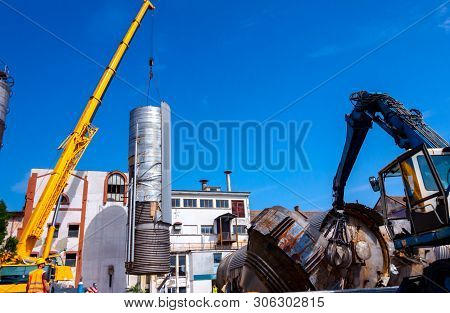 Loader machine with hydraulic grappling claw and crane are bringing down heavy metal silo in industrial complex. poster