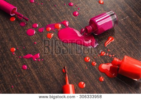Spilled Orange And Pink Nail Polishes On Wooden Background. Nail Polish Drops. Blot Of Nail Polish O