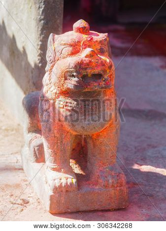 Mythological lion with vermillion red pigment powder guarding shrine at Kali Temple, worshiping Goddess Kali at Dhulikhel in Nepal