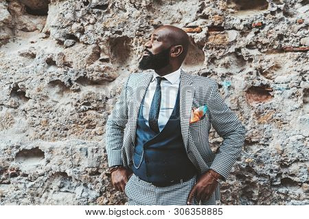 Handsome Bald Bearded Black Senior In An Elegant Costume In Front Of A Grungy Wall Outdoors; A Fashi