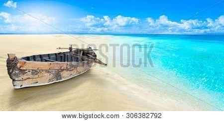 Old fishing boat on the seashore. Sandy beach.