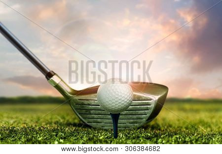 Golf Club And Ball On Grass With Under Sunset Sky Lights