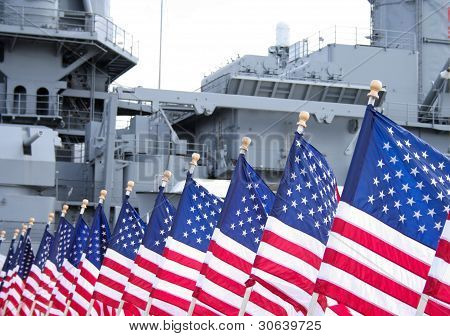 US flags flying in front of a US battleship