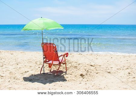 Green Sun Umbrella And Red Chaise Lounge On The Sandy Beach Against The Blue Sea Costa Blanca Of Spa