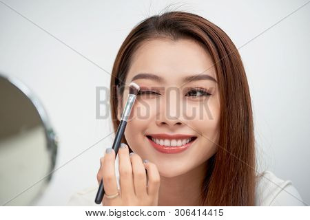 Close Up Of Beautiful Face Of Asian Young Woman Getting Make-up. Asian Woman Is Applying Eyeshadow O
