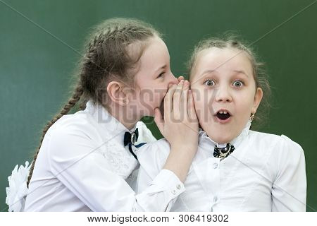 Schoolgirls Classmates Share Their Secrets Of Secrets Telling A Whisper In His Ear Near The Blackboa