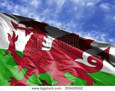 Waving Flag Of Wales Close Up Against Blue Sky