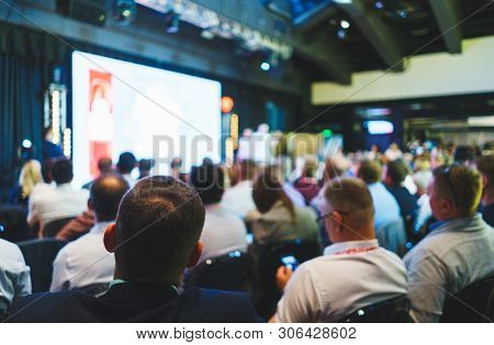 Conference Participants, Events, Presentations, Listen To The Speaker Sitting In Chairs. Rear View O
