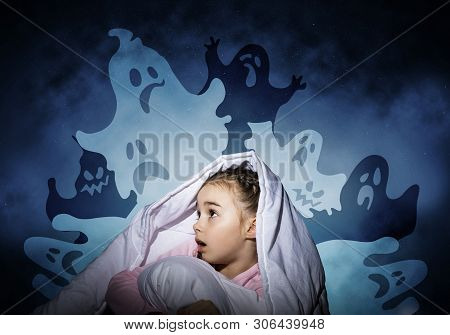 Excited Girl Hiding Under Blanket From Imaginary Ghosts. Scared Kid Sitting In His Bed At Home. Litt