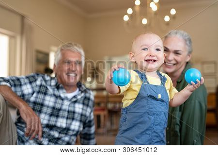Happy baby playing with balls on floor with grandparents in background. Cute boy standing and holding toy while looking up. Excited toddler enjoying playing with senior man and old woman at home.
