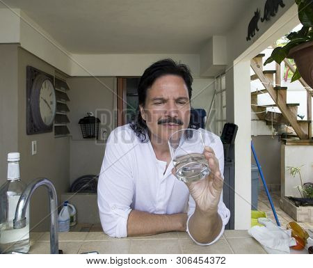 Hispanic Mam Looking At And Holding Glass Of Water.