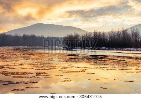 River In Mountain At Winter Sunset. Floating Melting Ice. Cloudy Sky Reflecting In The Water Surface
