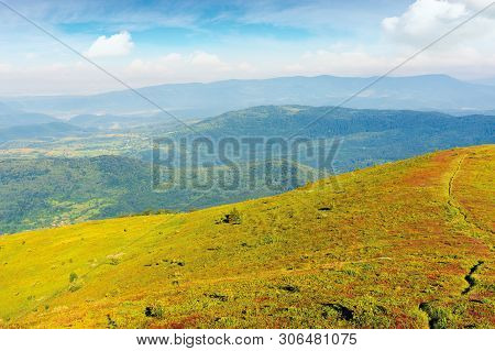 Grassy Slope Of A Hill In Morning Light. Summer Mountain Scenery. Blue Sky With Clouds Above The Dis