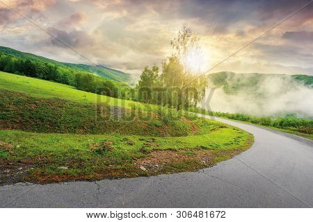 Road Down The Hill At Sunrise. Sun Light Come Through The Tree. Cloudy Sky Above The Distant Mountai