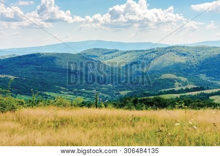 Summer Countryside In Mountains. Rural Field On The Hill. Village In The Valley. Ridge In The Distan
