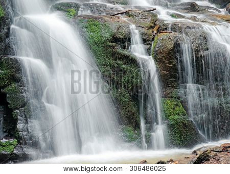 Close Up Of Waterfall Cascade Over The Mossy Rock. Beautiful Calm Nature Background. Freshness And P