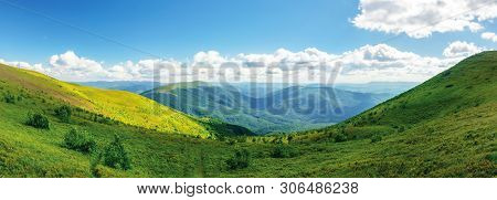 Panoramic Mountain Landscape In Summer. Grassy Meadows On Hills Rolling In To The Horizon. Sunny Aft