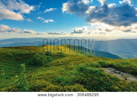 Summer Sunset In Mountains. Rocks Among The Grass On Rolling Hills. Sun Behind The Cloud Above The D