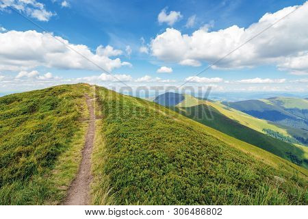 Path Uphill To The Mountain Top. Beautiful Summer Scenery With Dynamic Cloud Formations On A Blue Sk