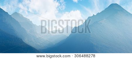 Panorama Of Mountain Ridge. Bright Scenery In Afternoon Hazy Light. Sky With Fluffy Clouds. Valley B