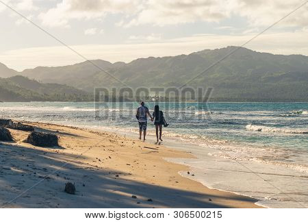 Couple Of Travelers Walking On Tropical Beach In Sunset. Vintage Photo Of Young Couple Traveler In V