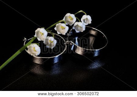 Brilliant Round Wide Metal Earrings And White Lily Of The Valley Flower.