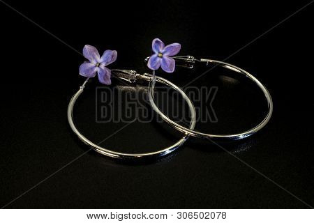 Shiny Round Thin Metal Earrings And Lilac Flowers.