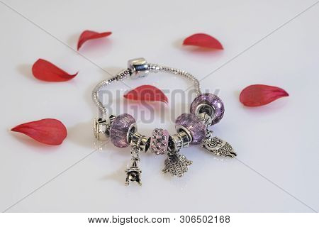 Beautiful Shiny Metal Bracelet And Red Flower Petals.