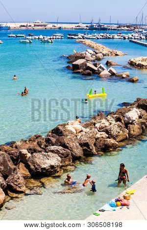 Otranto, Italy. July 30, 2015: Ionian Sea With Rocks, Harbor, Boats And People On Vacation. Detailed