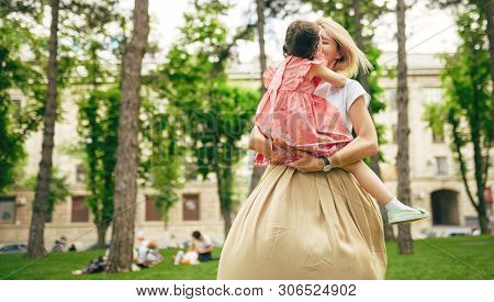 Horizontal Image Of Happy Daughter Playing With Her Mother In The Park. Loving Mother And Her Chid S