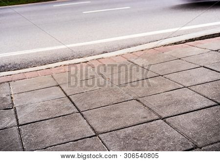 The Road Side Pathway Is Paved With Square Blocks Of Concrete