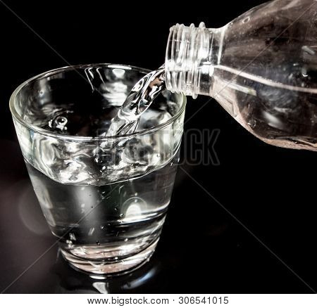 Pour Water From The Bottle Into The Glass