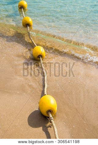 Floating Buoy And Rope Dividing The Area On The Beach