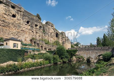 Bridge Over Alzette River In Luxembourg City And View At Medieval Fortification Wall