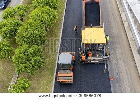 Road Works. Laying Asphalt In The City.  Shown Asphalt Paver, Asphalt Rink And Dump Truck With Aspha