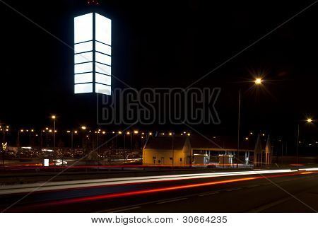 Night Photo Of Empty Billboard In The Shopping Park. Blurred Lights Of Cars In The Foreground.
