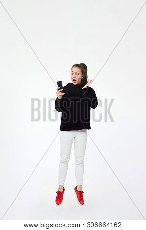 Young Pretty Brunette Girl In Black Hoodie, White Pants And Red Sneakers Hold Mobile Phone And Jumps