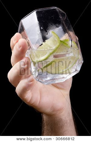 Male hand holding and showing of him gin drink with lime, isolated on black