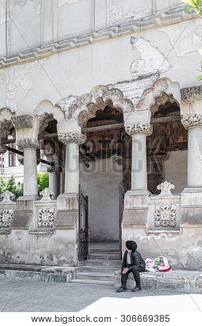 Bucharest, Romania - May 30, 2019: Poor Woman Sitting On The Stairs In Front Of The Coltea Church, O