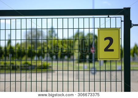 Number Two (2). Yellow Plate With The Number 2 On A Metal Fence. House Number Two Sign