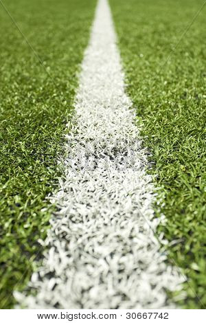 Green grass and sport lines painted at an outdoor playing field (artificial covering) - photographed with shallow DOF