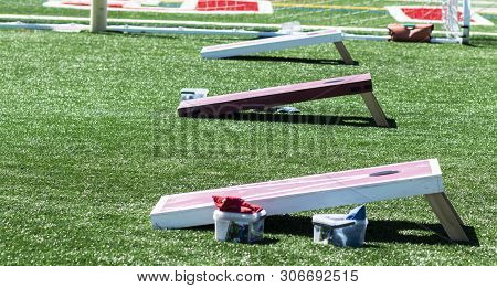 Three Homeaide Wooden Corn Hole Game Boards Are Set Up Side By Side On A Green Turf Field With Bean