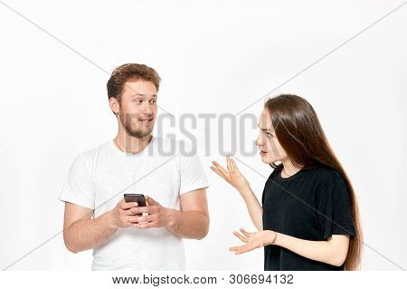 Studio Shot Of A Young Couple Quarreling. Woman Is Upset That Man Uses Phone All The Time Without Pa
