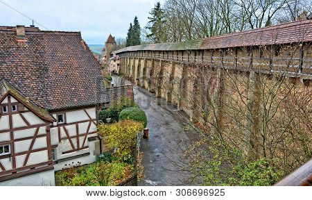 Ancient Stone Wall Surrounding The Old Town From The Wall. Medieval Half-timbered House With Tile Ro
