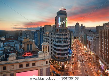 MADRID, SPAIN – MAY 13, 2018: Business shopping area on Gran Via at sunset with historical buildings and traffic.