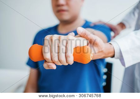 Physiotherapist Man Giving Exercise With Dumbbell Treatment About Arm And Shoulder Of Athlete Male P