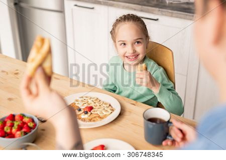Father eating crepe and enjoying breakfast with daughter, smiling beautiful girl listening to father and eating homemade crepe